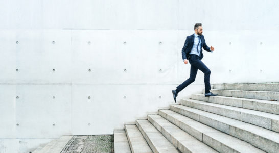 Young businessman running on stairs in the street